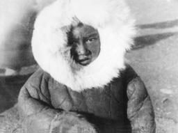 Ein Kind in einem sowjetischen Wintermantel mit Fell.